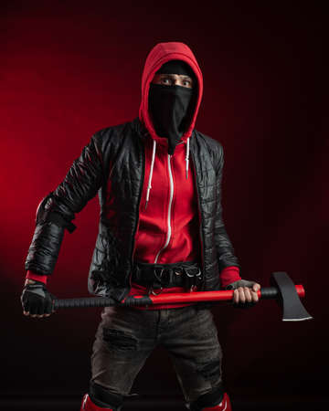 a man in a Balaclava and hoodie with an axe the image of a Protestant