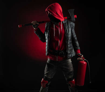 a man in a Balaclava and hoodie with an axe and a fire extinguisher the image of a Protestant