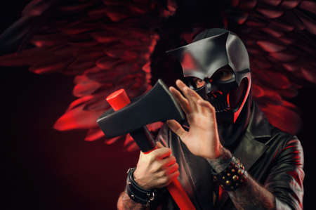 a man in a demon skull mask in a leather cloak with an axe on a background of black and red wings