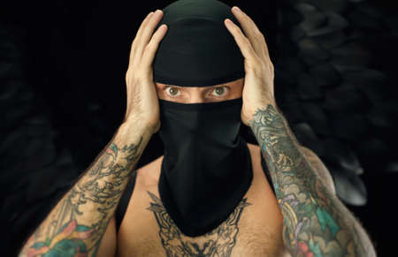 portrait of a guy in a balaclava with a torso in tattoos holding his head