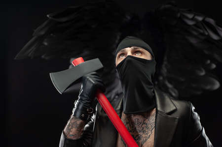 Portrait of a criminal guy in a balaclava in a leather jacket with an axe