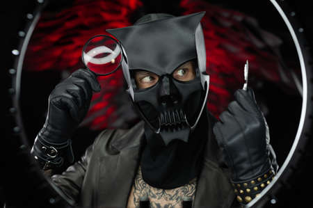 a man wearing a demon skull mask in a leather cloak with a magnifying glass and pills - doctor evil