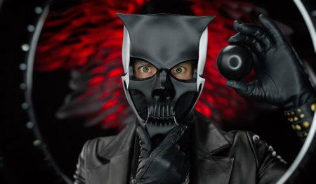 a man wearing a demon skull mask in a leather cloak