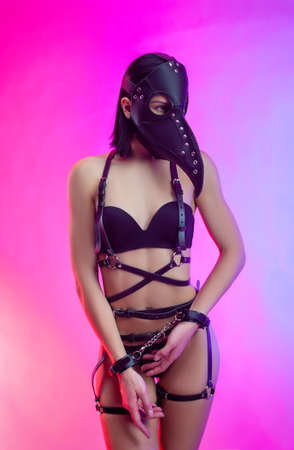 a woman in a doctor plague mask on leather belts and BDSM belts Stock Photo