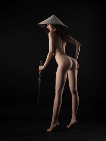 slender woman in an Asian triangular hat with a katana in her hand