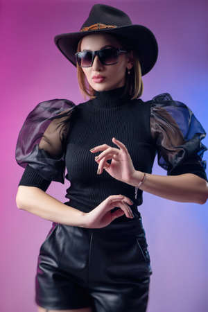 fashionable stylish woman in black clothes and hat poses with neon background