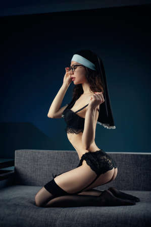 photo of a girl on the couch in stockings and a headdress nun