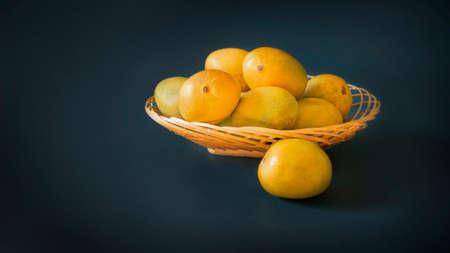 mangoes in basket blue dark background Reklamní fotografie
