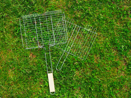steel grid for grill barbecue lying on green grass