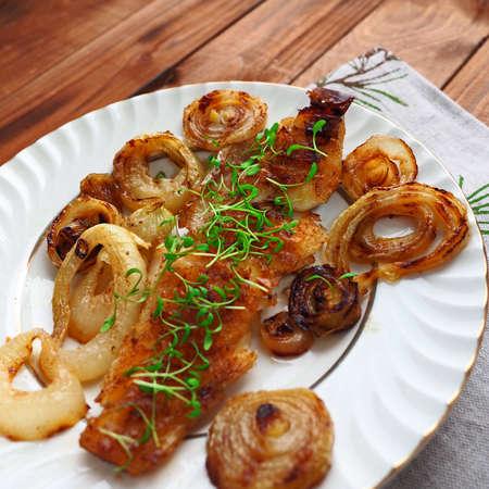 Visfilet gegrild met uien op plaat. Rustieke houten achtergrond Stockfoto