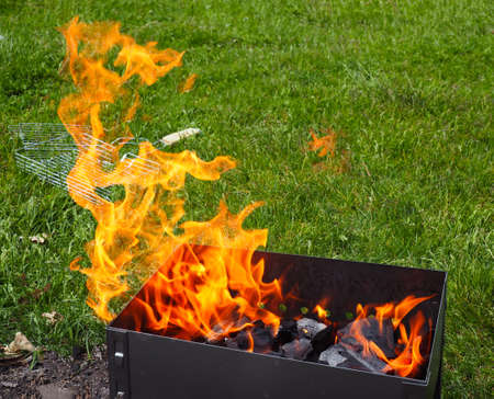 Close up of barbecue grill with roaming fire against the background of green grass