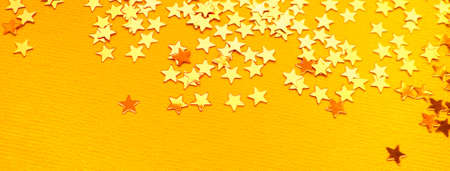 Golden stars glitter on orange paper background. Festive holiday bright backdrop
