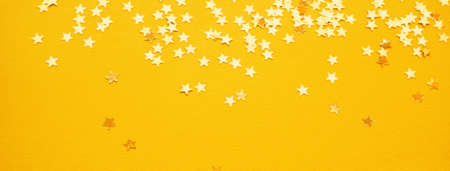 Golden stars glitter on yellow paper background. Festive holiday bright backdrop Stock Photo