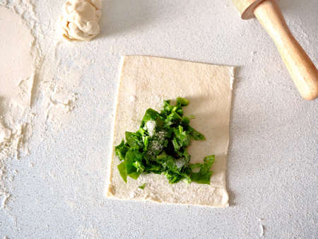 Process of making a sweet puff pastry with sorrel. Homemade buns with garden greens