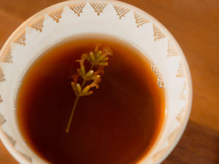 Close up image of mug with blooming lavender sprig in black tea. Stock Photo