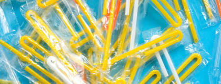 Pile of yellow drinking straws on a blue background. Top view of many plastic bendy cocktail straws, abstract backdrop. Social media banner or header. Imagens
