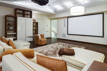 Theater room in luxury home with white big leather sofa and chairs