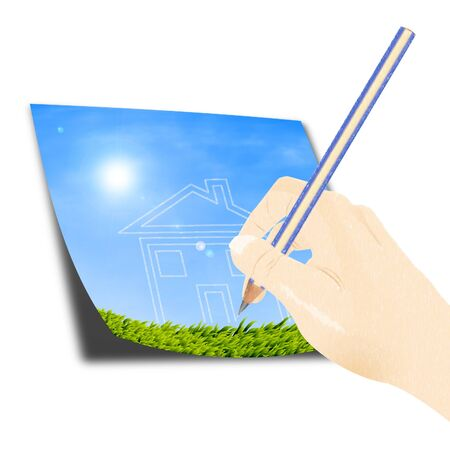 Hand with a pencil drawing a house of dream against blue sky and green grass  photo