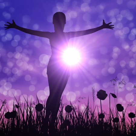 Silhouette of a young woman with raised hands on the meadow. Foto de archivo