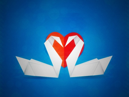 Two white paper swans and red heart on blue background. photo