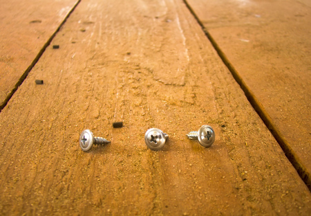Three small screws  left on wooden floor. photo