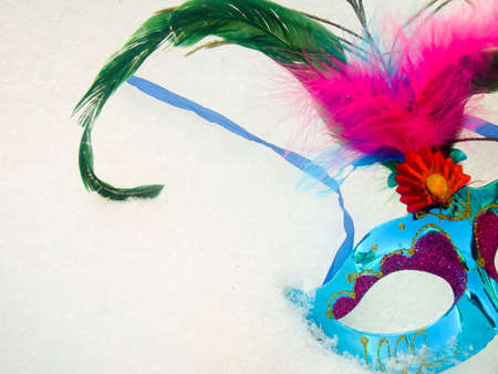 Blue carnival mask with feather on snow background. photo