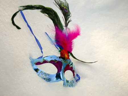 Blue carnival mask with feather on snow background.