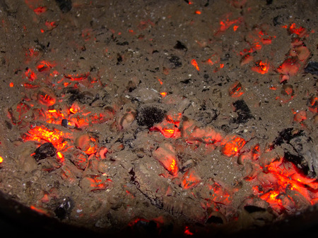 Glowing ash and embers after bonfire in fireplace. photo