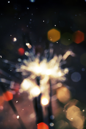 Bengal fire, sparkler and colorful bokeh with blurred snow, christmas, new year background. photo