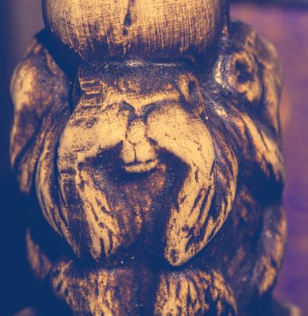 statuette: Macro of small wooden statuette of monkey, vintage photo effect.