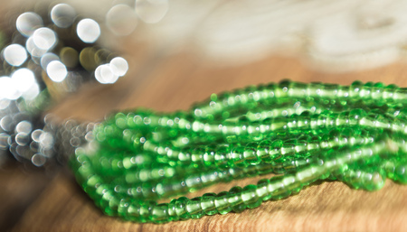 bugle: Decorative green color bugle beads with bokeh effect.