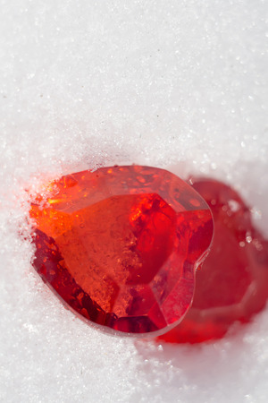 plastic heart: Shiny plastic heart of red color on white snow background.