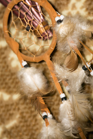 magical equipment: Background with dream catcher with brown feathers, close up photo.