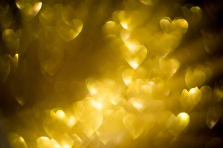 Festive background with defocused golden glitters, bokeh in a shape of a heart.
