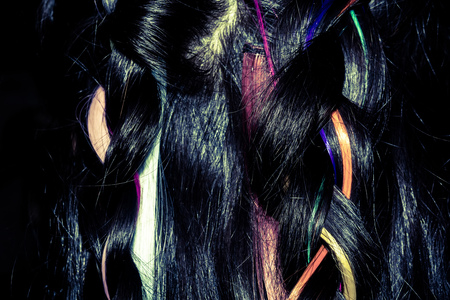 dark brown hair: Dark brown hair with colorful synthetic clip in extensions macro. Stock Photo