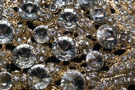 Diamonds in different sizes, golden jewelry close up background.