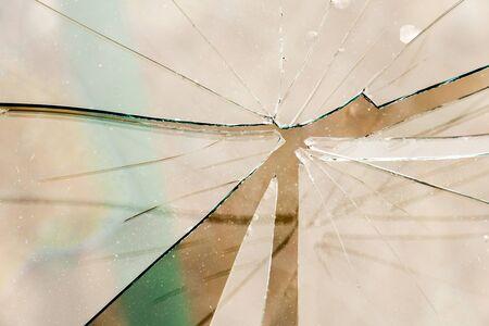 splinters: Sharp glass hole cracks splinters, broken glass by the street.