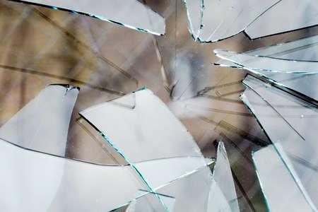 Sharp glass hole cracks splinters, broken glass by the street.