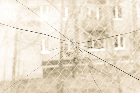splinters: Sharp glass hole cracks splinters, broken glass by the street, sepia tone.