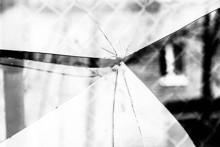grayscale background: Sharp glass hole cracks splinters, broken glass by the street, grayscale background.
