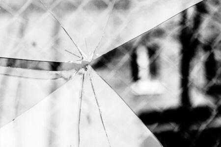 splinters: Sharp glass hole cracks splinters, broken glass by the street, grayscale background.