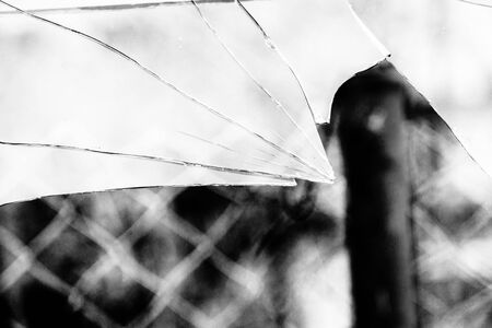 grayscale background: Sharp glass hole cracks splinters, broken glass by the street, grayscale background.