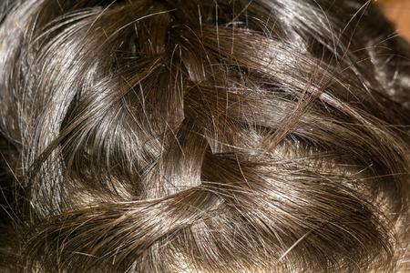 dark brown hair: Braided dark brown hair close up background.