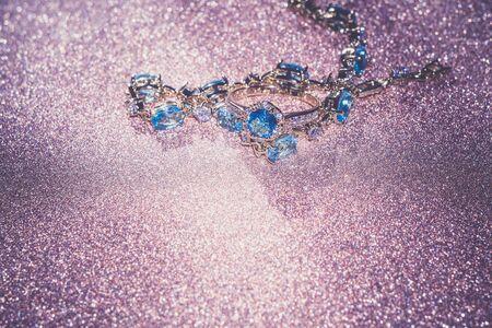 karat: Decorative golden bracelet with light blue topaz on glittering background.