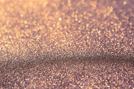 lux: Decorative brown glitter texture macro, defocused background, bokeh.