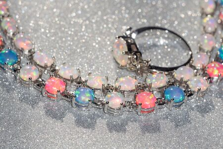 opal: Fashion bracelet with multicolored fire opal stones on glittering background.