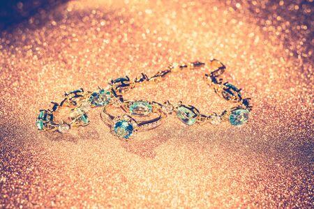 topaz: Decorative golden bracelet with light blue topaz on glittering background.
