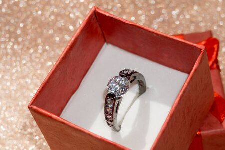 jewel case: Diamond ring of black gold in a red gift box on glittering background.