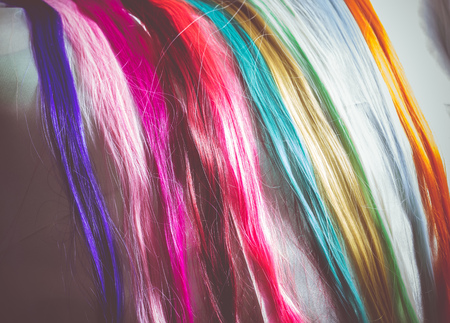 synthetic: Synthetic hair extensions of different colors close up background.