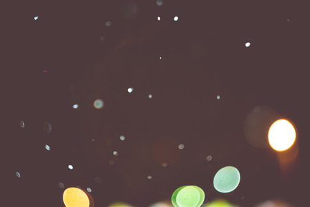 wintery: Blurred night lights and snowfall, bokeh effect filtered background. Stock Photo